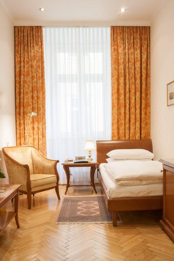 Einzelzimmer mit Bett und Sessel