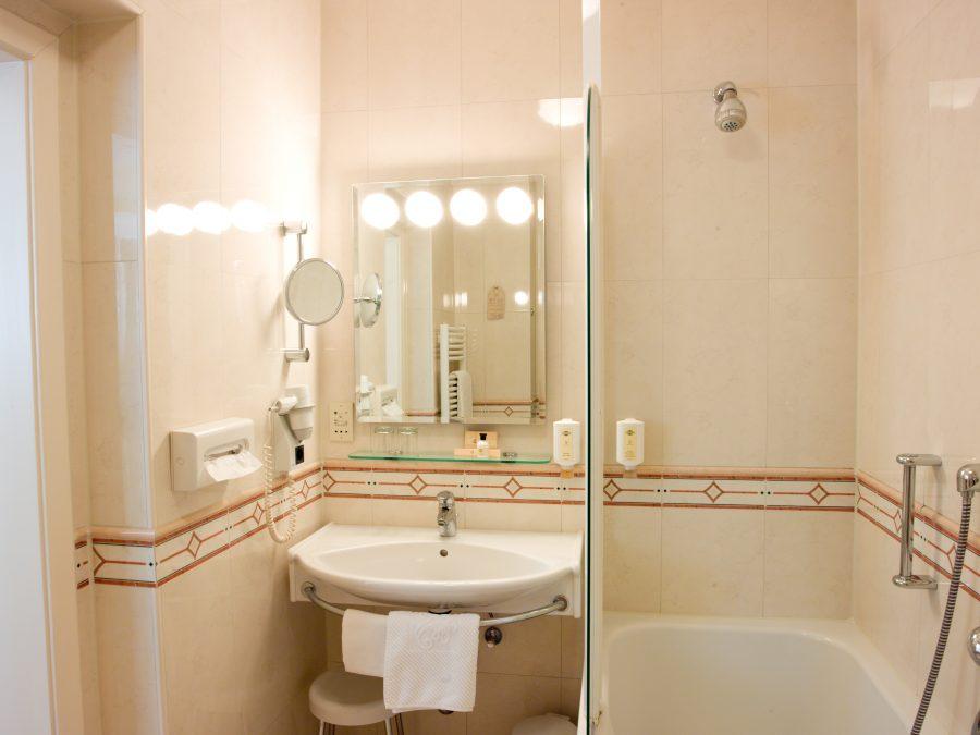 Hotelbadezimmer mit Waschtisch, Spiegel und Badewanne