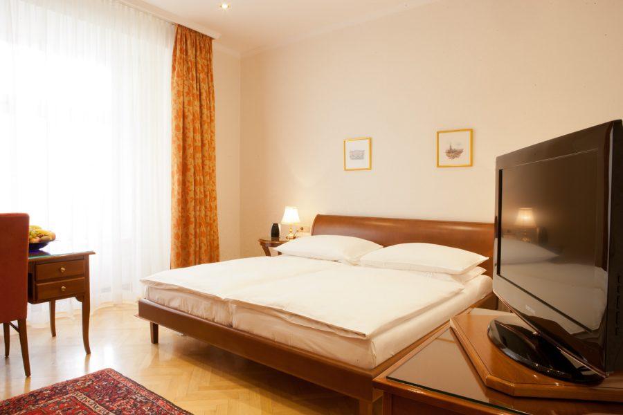 Hotelzimmer mit Doppelbett und großem Fernseher