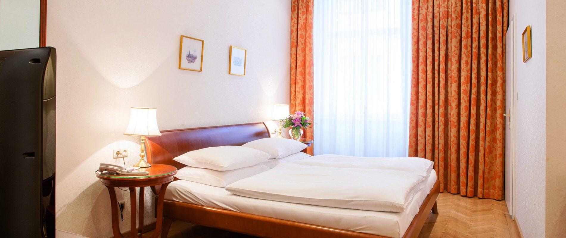 Hotelzimmer mit Doppelbett und roten Vorhängen