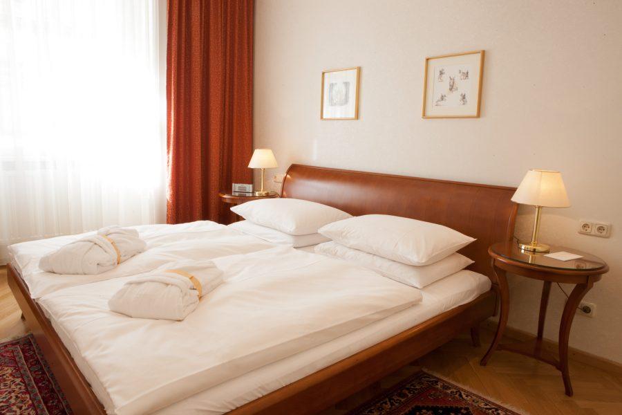 Doppelbett mit Bademänteln und Nachtischen