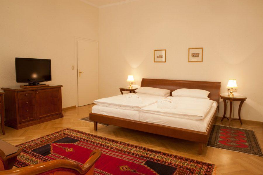 Hotelzimmer mit Doppelbett und Fernseher