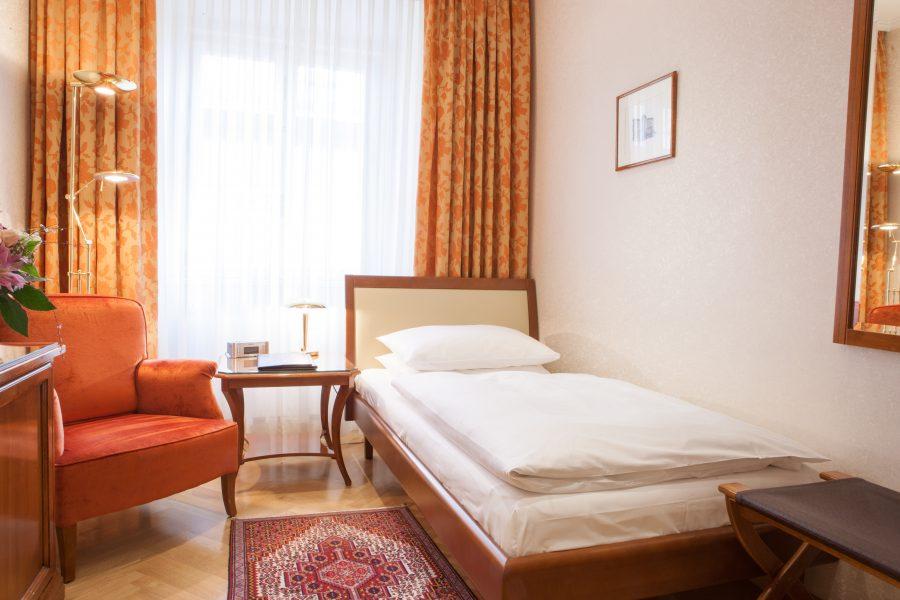 Einzelzimmer mit rotem Sofa und Kofferablage