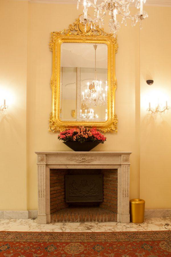 Goldener Spiegel über Kamin mit Blumengesteck