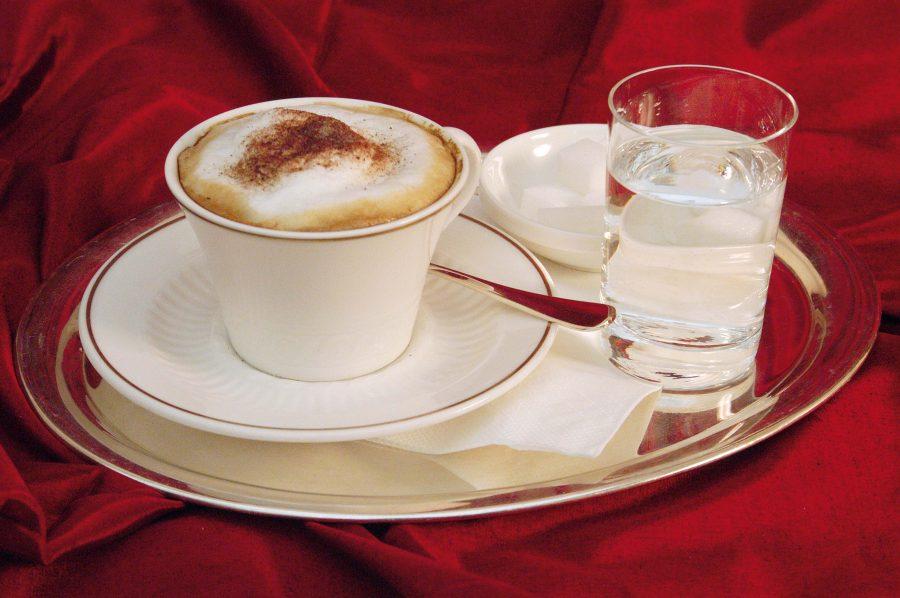Kaffee und Wasserglas auf Silbertablett