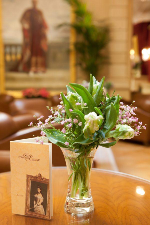 Blumenstrauß und Menükarte auf Holztisch in der Lobby