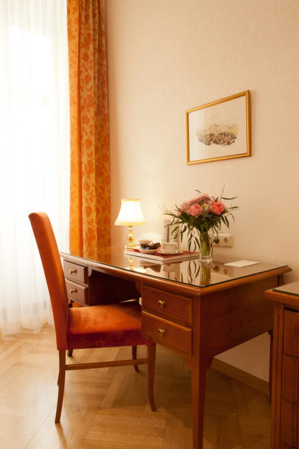 Schreibtisch im Hotelzimmer mit Blumen und Kaffeeset