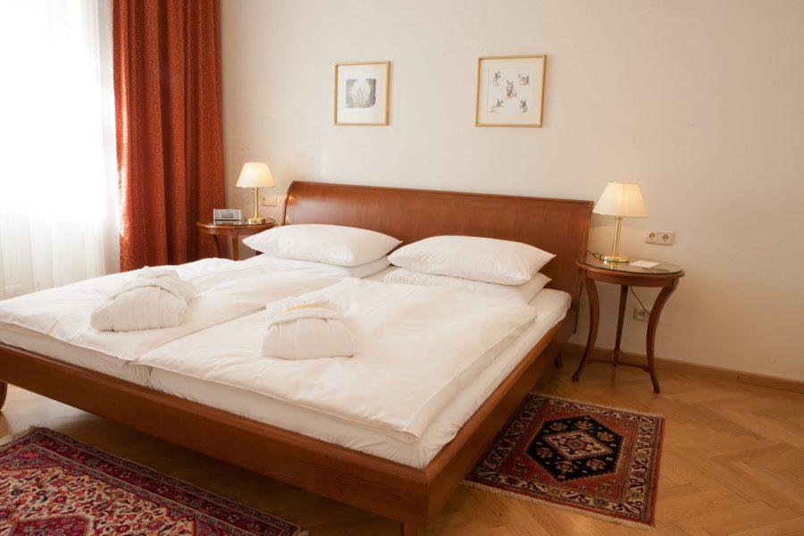 Hotelzimmer mit Doppelbett und Bademäntel