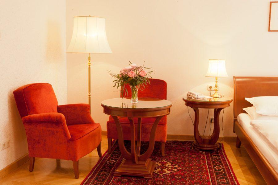 Rote Sitzmöbel mit Tisch und Blumenstrauß
